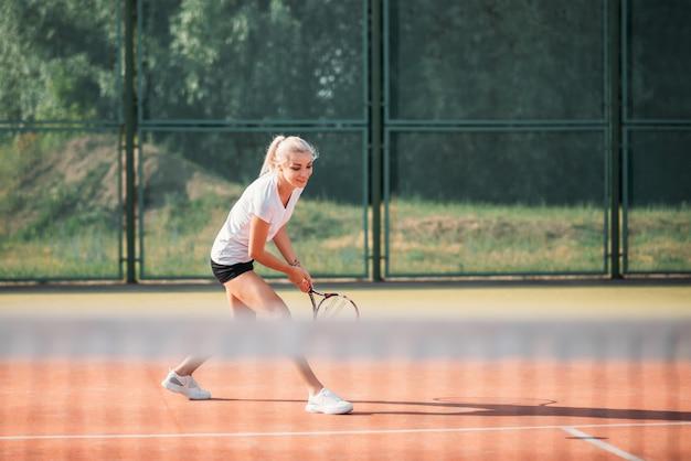 Belle jeune femme jouant au tennis sur un court. mode de vie sportif sain