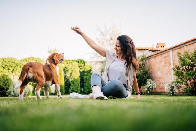 Belle jeune femme jouant avec son chien beagle dans la cour.