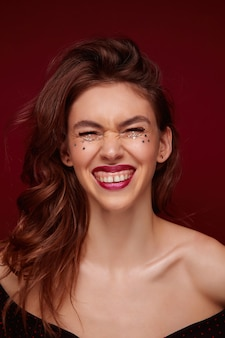 Belle jeune femme joyeuse aux cheveux ondulés bruns riant joyeusement et montrant ses dents blanches parfaites, portant du maquillage du soir et de petites étoiles argentées sur son visage, isolées