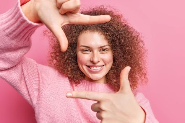 Belle jeune femme joyeuse faisant des sourires de geste de cadre de main porte joyeusement un pull décontracté fait des photos avec les doigts quelque chose à l'esprit crée un chef-d'œuvre se dresse sur un mur rose.
