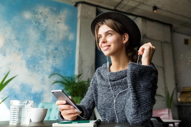 Belle jeune femme joyeuse habillée en pull et chapeau assis dans une chaise à la table du café, écouter de la musique avec des écouteurs, intérieur élégant, prendre des notes