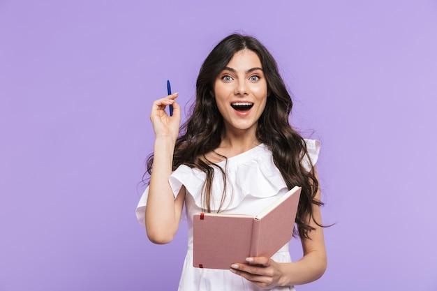 Belle jeune femme joyeuse portant une tenue d'été isolée sur un mur violet, prenant des notes dans son journal