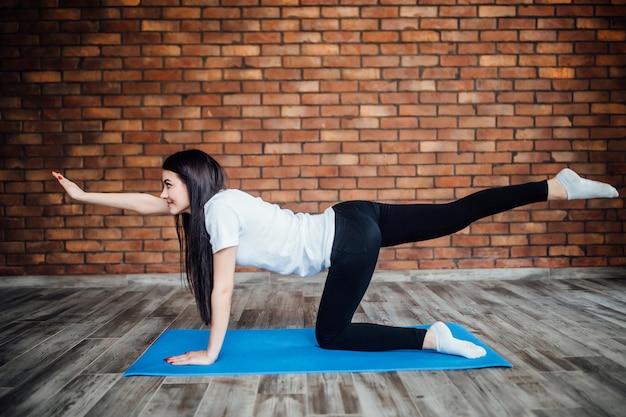 Belle jeune femme joyeuse travaillant à l'intérieur. beau modèle faisant des exercices sur tapis bleu dans la salle avec des murs