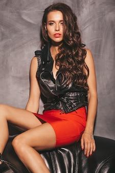 Belle jeune femme en jupe et veste rouge tendance d'été.