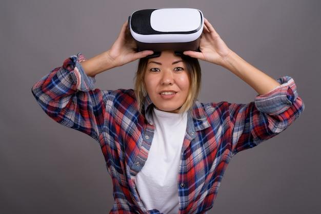 Belle jeune femme kazakhe à l'aide d'un casque de réalité virtuelle à nouveau