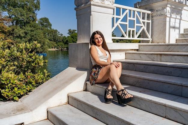 Belle jeune femme latina assise sur les marches d'un escalier en marbre blanc au repos au soleil du matin.