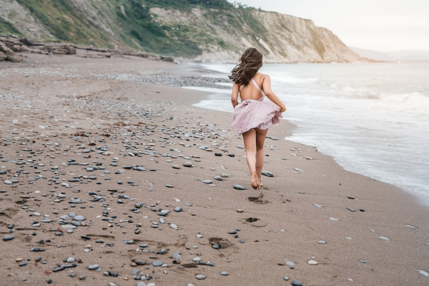 Belle jeune femme latine aux longs cheveux noirs, courant le long d'une plage au coucher du soleil, vêtue d'une élégante robe rose