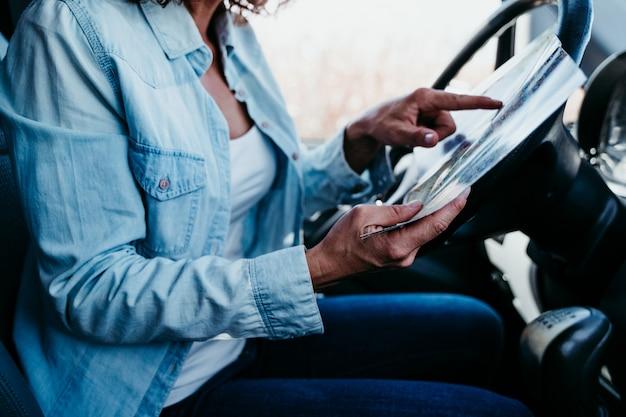 Belle jeune femme lisant une carte dans une voiture. concept de voyage