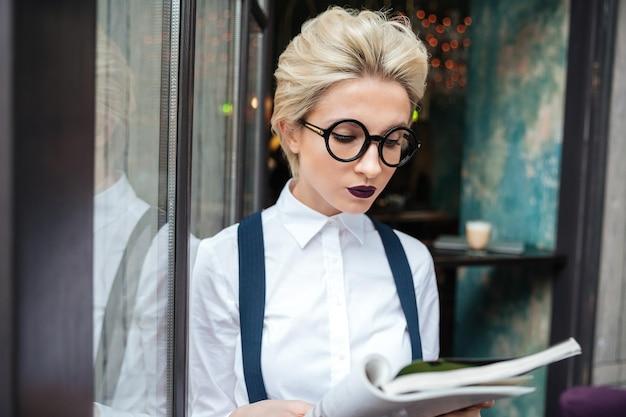 Belle jeune femme lisant un livre au café
