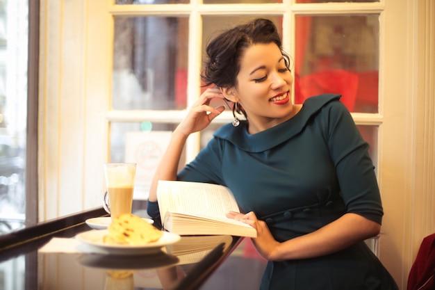 Belle jeune femme lisant un livre dans un bar