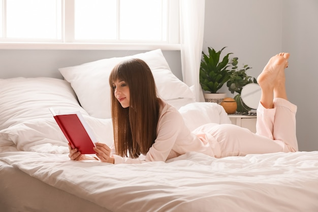 Belle jeune femme lisant un livre dans la chambre