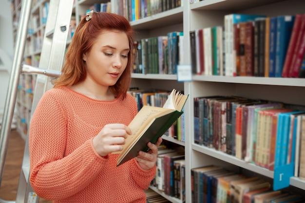 Belle jeune femme lisant un livre à la librairie