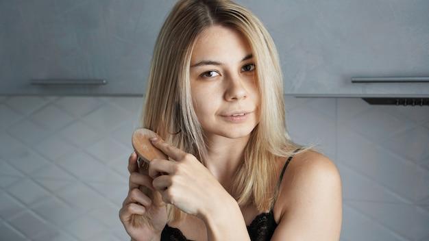 Belle jeune femme lissant ses cheveux blonds à la maison gris flou