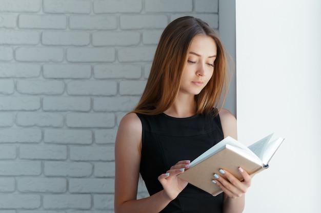 Belle jeune femme avec livre près de mur de briques.