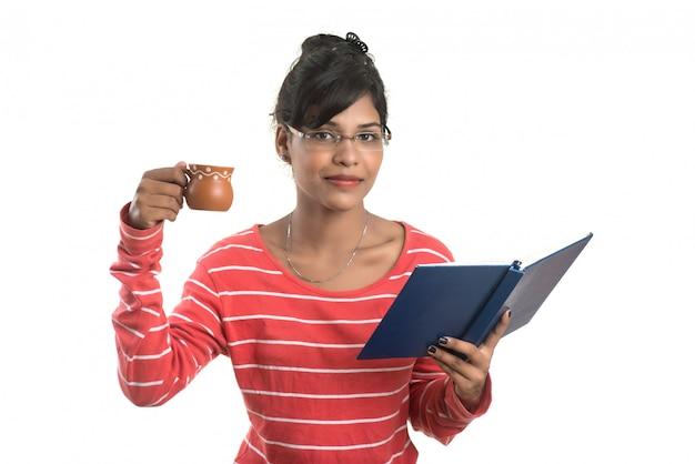 Belle jeune femme avec livre et tasse de café posant sur un mur blanc.
