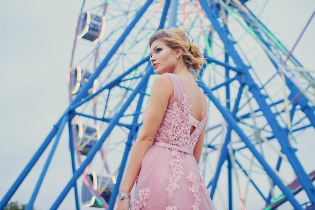Belle jeune femme en longue robe de soirée rose chemin de marche dans le parc. portrait de style de mode de magnifique belle fille à l'extérieur près de la grande roue