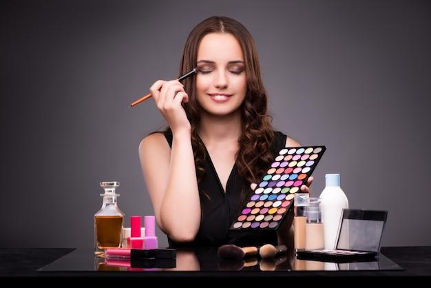 Belle jeune femme lors d'une séance de maquillage