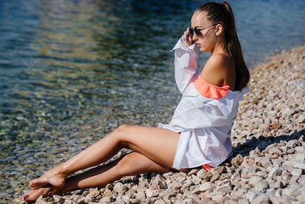 Une belle jeune femme à lunettes et un bikini est assise au bord de l'océan sur fond d'énormes rochers par une journée ensoleillée. tourisme et voyages touristiques.