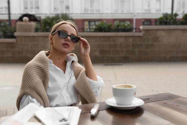 Belle jeune femme avec des lunettes dans un café de la rue