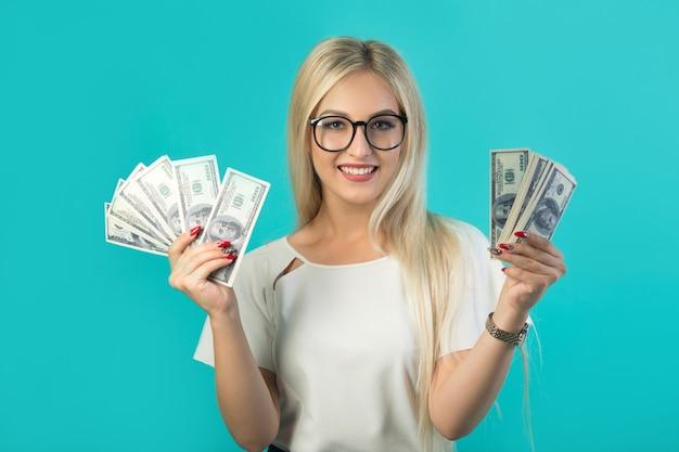 Belle jeune femme à lunettes avec des dollars dans ses mains