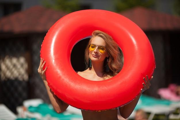 Belle jeune femme à lunettes de soleil avec cercle de natation