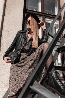 Belle jeune femme avec des lunettes de soleil et un chapeau dans une robe de mode avec une élégante veste en cuir noire posant sur un escalier en métal au soleil