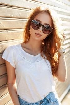 Belle jeune femme à lunettes de soleil et chemise blanche appuyée contre le mur en bois.