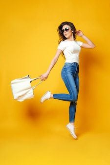 Belle jeune femme à lunettes de soleil, chemise blanche, jeans bleu sautant avec sac sur le fond jaune