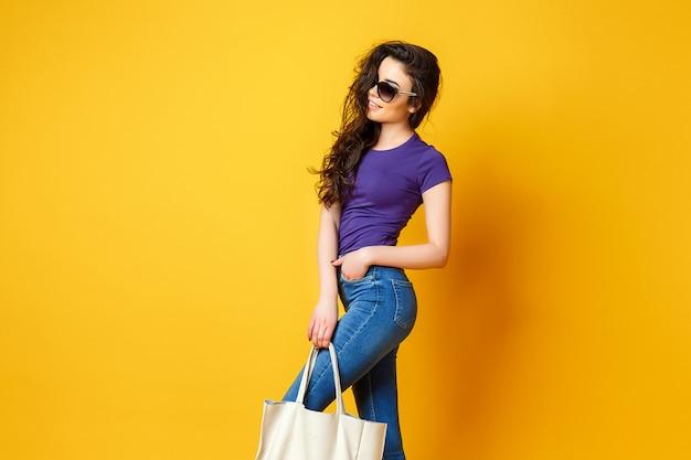 Belle jeune femme à lunettes de soleil, chemise pourpre, blue jeans posant avec sac sur fond jaune