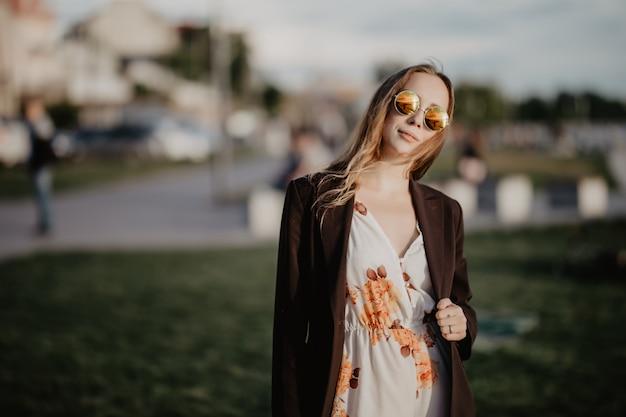 Belle jeune femme à lunettes de soleil dans la ville au coucher du soleil