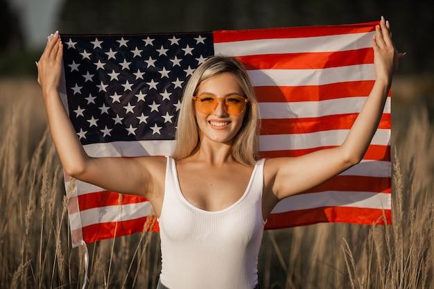 Belle jeune femme à lunettes de soleil avec drapeau américain