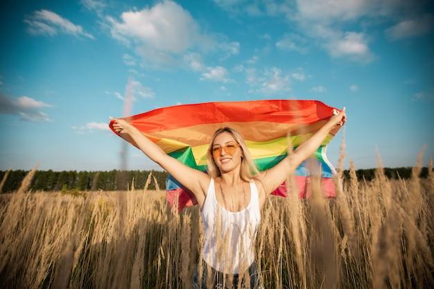 Belle jeune femme à lunettes de soleil avec drapeau lgbt dans un champ