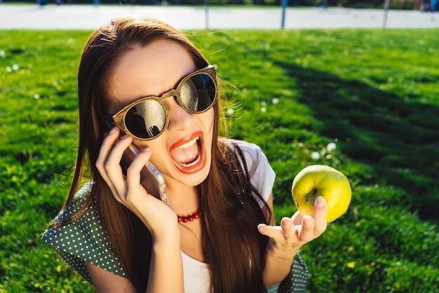 Belle jeune femme à lunettes de soleil est assise sur la pelouse avec de l'herbe verte brillante, parlant au téléphone, criant