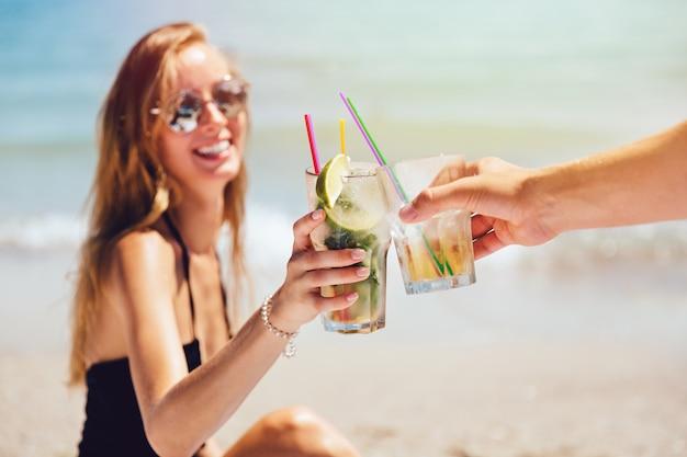 Belle jeune femme en lunettes de soleil et maillot de bain, grillage avec cocktail