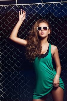 Belle jeune femme à lunettes de soleil près de la clôture. de beaux cheveux sains. des lunettes de soleil. t-shirt vert