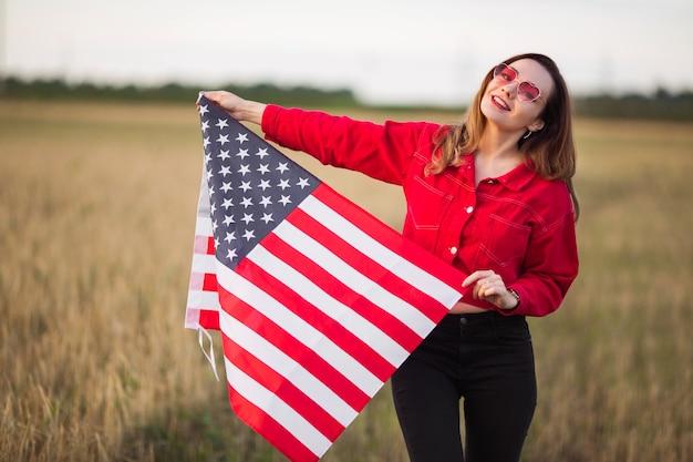 Belle jeune femme à lunettes de soleil roses avec drapeau américain