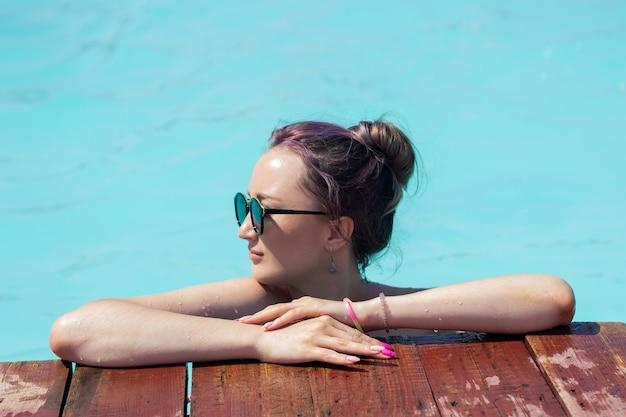 Une belle jeune femme à lunettes de soleil se détend au bord de la piscine