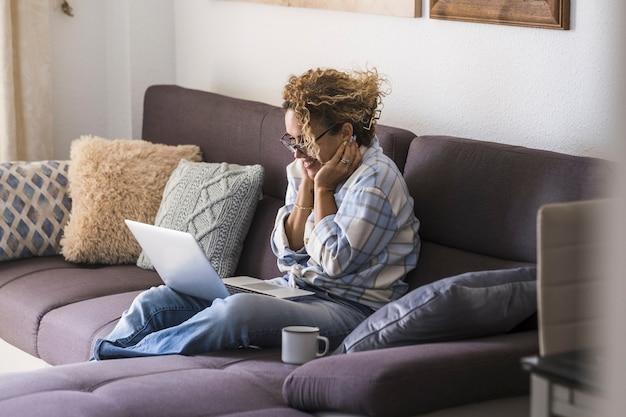 Belle jeune femme à lunettes travaillant sur ordinateur portable tout en buvant du café assis sur le canapé. femme d'affaires surprise chez les occasionnels travaillant à domicile. femme étonnée par le succès en ligne à la maison