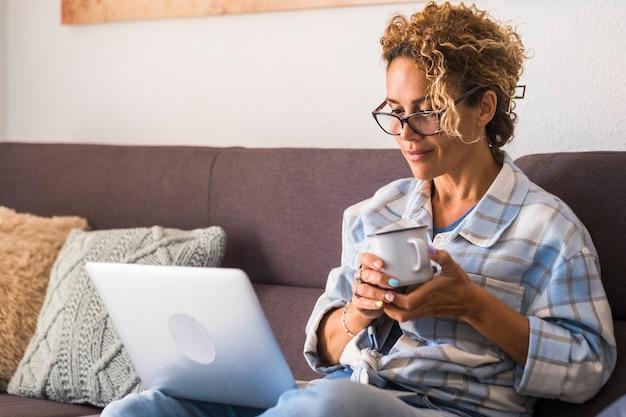 Belle jeune femme à lunettes travaillant sur ordinateur portable tout en buvant du café assis sur un canapé à la maison. businesswoman in casuals et lunettes travaillant à domicile sur ordinateur portable.