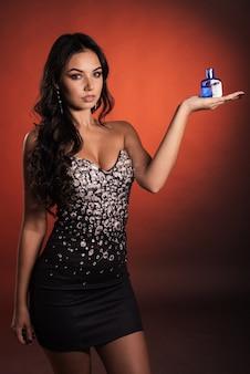 Belle jeune femme luxueuse dans une robe avec strass posant avec parfum