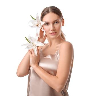 Belle jeune femme avec des lys frais sur blanc