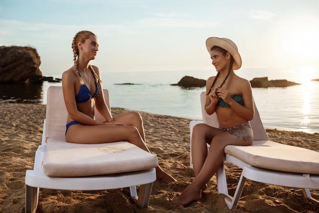 Belle jeune femme en maillot de bain assis sur des chaises près de la mer