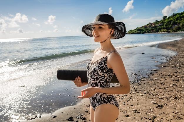 Belle jeune femme en maillot de bain et chapeau va faire du yoga.
