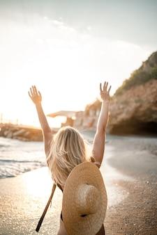 Belle jeune femme en maillot de bain noir et chapeau avec des lunettes se promène le long de la plage en turquie au coucher du soleil. le concept de loisirs en mer. mise au point sélective