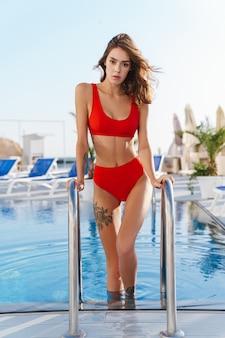 Belle jeune femme en maillot de bain rouge regardant à l'avant et sortant de la piscine à la plage de luxe