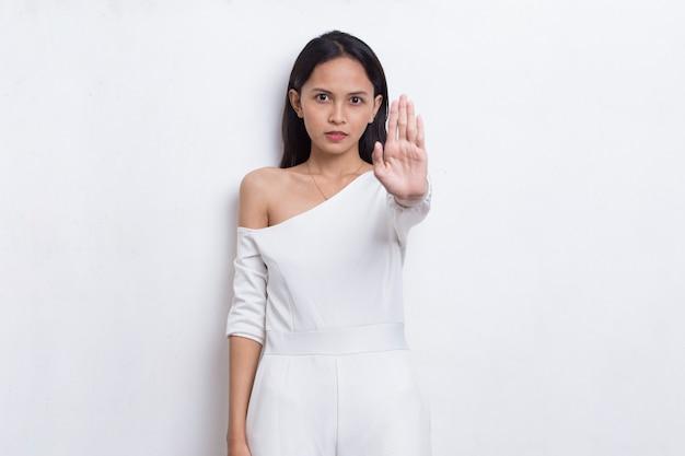 Belle jeune femme avec la main ouverte faisant un panneau d'arrêt avec un geste de défense d'expression sérieuse