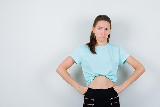 Belle jeune femme avec les mains sur la taille en t-shirt, pantalon et à la recherche de grincheux. vue de face.