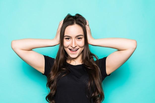 Belle jeune femme avec les mains sur la tête debout sur un mur bleu