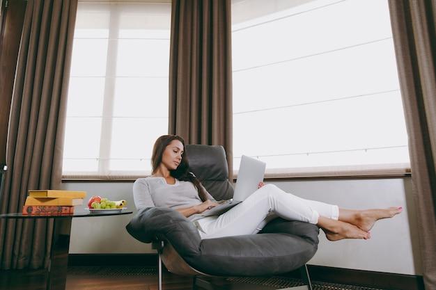 La belle jeune femme à la maison assise sur une chaise moderne devant la fenêtre, se relaxant dans son salon et travaillant avec un ordinateur portable