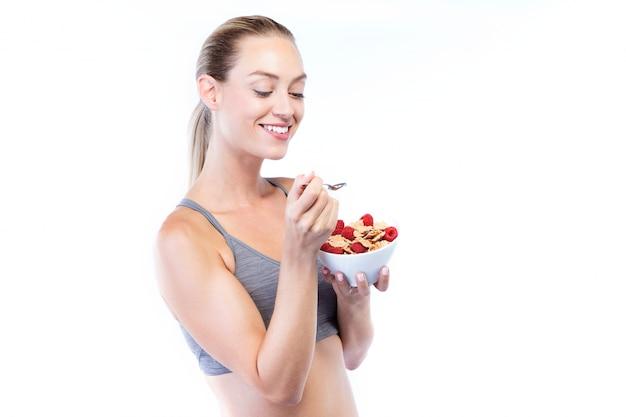 Belle jeune femme mangeant des céréales et des fruits sur fond blanc.
